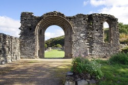 A stone archway is nearly all that remains of this ruined abbey in Wales