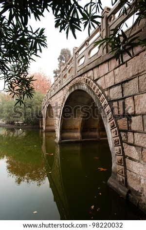 A stone bridge reflects in the water in a park in Shanghai