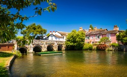 A stone bridge spans the River Avon Christchurch Dorset England on a hot summer day