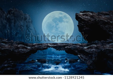 A stone bridge with a waterfall on the beautiful full moon night. #1128921245