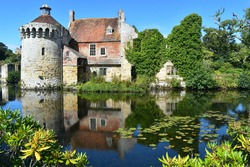 A stone centuries old British medieval castle facade amongst lush greenery with its reflection in water. It includes a tower residential buildings and an estates office all dominated by a banquet hall