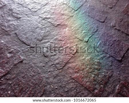 A stone floor lit by a window. A random reflection creates a rainbow on it. #1016672065