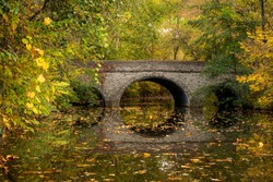 A stone foot bridge standing in tranquil water during peak Autumn color in late October.