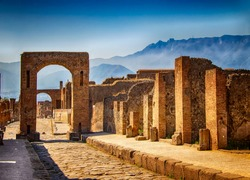 A stone gate and ruin of the city. Behind it is blue sky and big mountains. It is situated in Pompei, Italy in Europe.