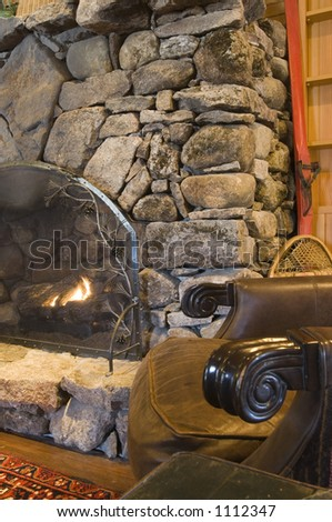 A stone hearth fireplace with section of a leather chair