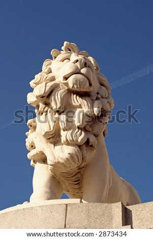 a stone lion on a plinth on the embankment in London