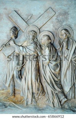 A stone relief depicting the 4th Station of the Cross where the condemned Jesus meets His mother as he carries the cross towards Calvary.
