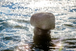 A stone sculpture stands in seawater