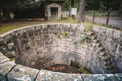A stone staircase leads down a round stone wall to a disused water gallery. Until 1998 this tunnel was relevant for water supply.