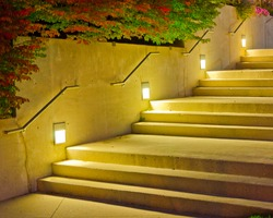 A stone staircase with lamps at night