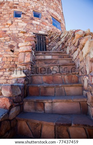 A stone stairway leads up to a barrier of wood and grout on the Desert View observation tower at the Grand Canyon in Arizona.