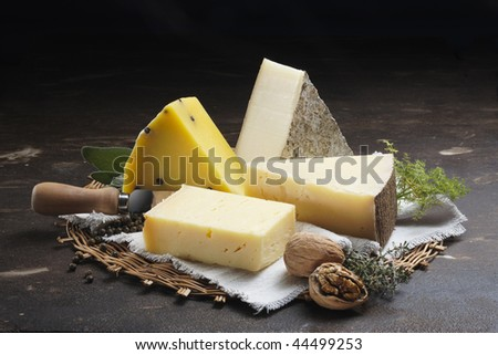 A Stone table in a farm with cheeses nuts and spices