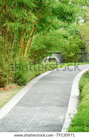 A stone walkway with bamboo in both side in traditional Chinese garden