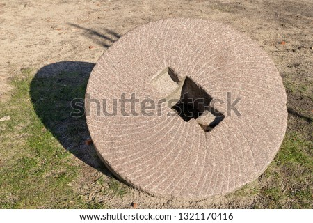 A stone wheel for grinding grain. Old mill grinders. Place - a monument in a local village. Season winter. #1321170416