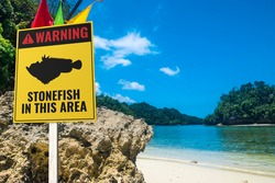 A stonefish warning sign at a rocky beach. A stern warning for barefoot bathers. Tropical beach setting.