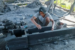 A stonemason makes an altar to a Hindu temple on the island of Bali in Indonesia. A man joins and glues stone slabs. Man Chiseling Stone with Hand Tools