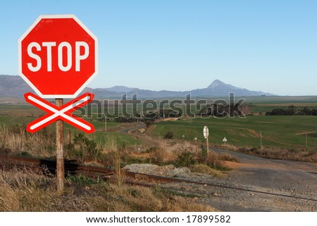 A stop sign at a rail road crossing