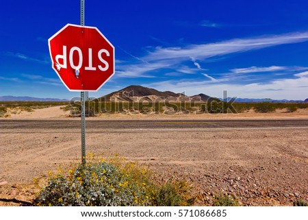 A Stop Sign in a remote area of Arizona, vandalized and shot up to the point of barely hanging onto its pole.