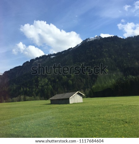A store room is located among green field with green mountain and blue sky