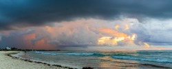 A storm with black clouds and sunlight blowing over a beach in Mexico.