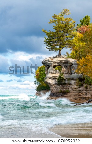 A stormy Lake Superior drives waves crashing against Chapel Rock as ominous skies and autumn colors create a stunning background