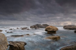 A stormy scene unfolds as the Atlantic Ocean meets the shoreline at the Cape of Good Hope and the turbulent waves rush towards the mushroom shaped rock in a slow motion long exposure landscape scene