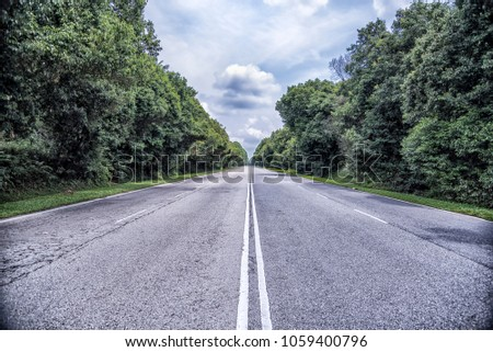 a straight roadway surrounded by trees
