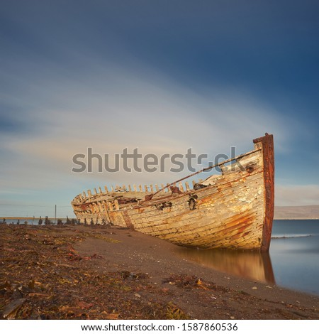 A stranded old wooden boat. It is already very weathered. a stranded old wooden boat. The water retreats to the ebb.
