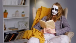 A strange man metal head rocker with a painted face emotional reads a book in a cozy home interior. Stay at home. Social exclusion