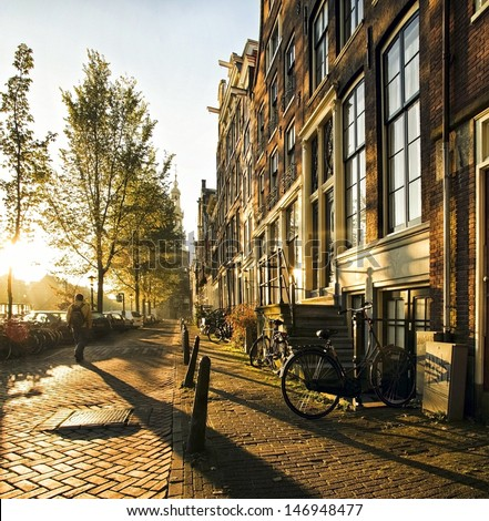 A stranger in the streets of the city Amsterdam, accompanied by long shadows, strolled between the canals and residential houses during this atmospheric sunset. #146948477