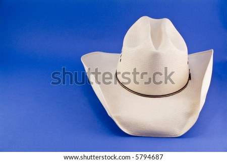 A straw cowboy hat taken on a blue background.