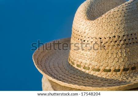 A straw hat sitting beside blue water - stock photo