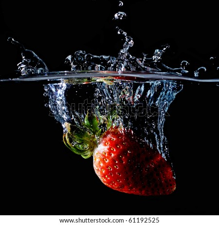 A strawberry splashing into water