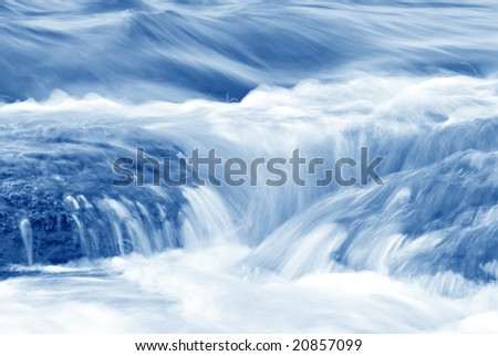 A stream flowing over rocks in shades of blue.