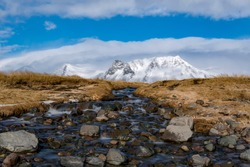 A stream flows with a mountain rising in the background at ytri-tunga beach in Western Iceland.