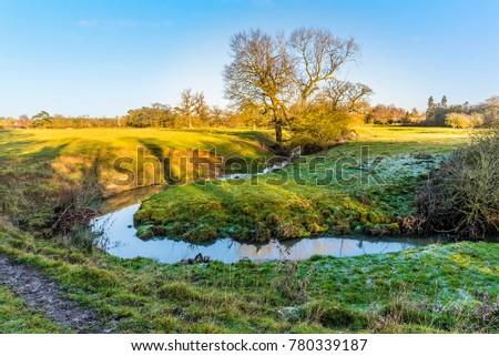 A stream meanders across a meadow near Lubenham, UK on a bright winters day