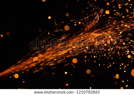 A stream of bright sparks from metal cutting.  #1210782865