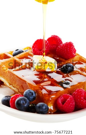 A stream of golden Canadian maple syrup adds the finishing touch to a delicious breakfast of belgian waffles with fresh raspberries and blueberries.  Shot on white background.
