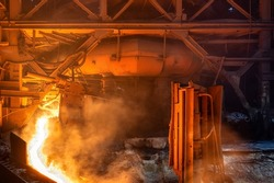 A stream of hot metal, molten steel flowing along a guide chute.