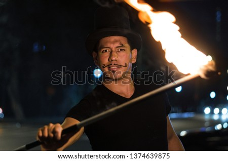 A street artist who makes a show in Lima - Peru, juggling a stick with fire at traffic lights stops, in front of stopped cars #1374639875
