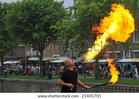 A street entertainer breathing fire in front of a large crowd of people,Schravendeel,Holland - stock photo