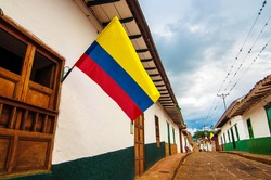 A street in Barichara, Colombia with Colombian flags.