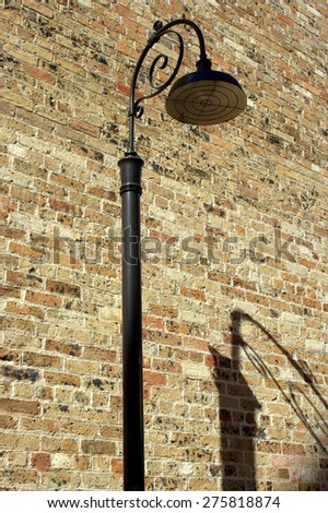 a street lamp and its shadow by an old brick wall on a lane in the Rocks, Sydney