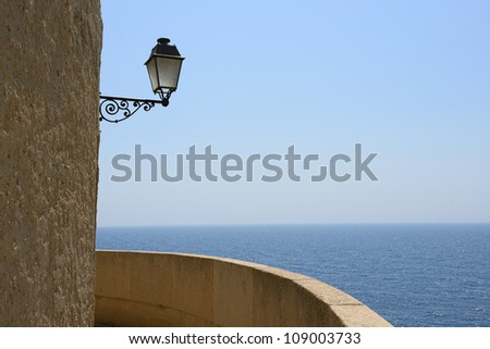 A street lamp attached to a rock wall, Monte Carlo, Monaco