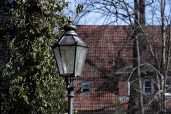 A street lantern or cast iron lamp on blurred background of a dark green tree and a tile roof. Historical scenery of a European city or town. Retro illumination equipment.