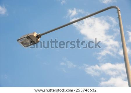 a street light pole with a blue sky background.