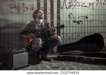 A street musician playing on guitar in the underpass. Vagrant lifestyle. Playing in the underpass to make a living. Unemployed musician. Future rock star. Horizontally framed shot.