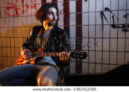 A street musician playing on guitar in the underpass. Vagrant lifestyle. Playing in the underpass to make a living. Unemployed musician. Future rock star. Photo.