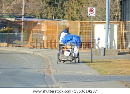 A street person uses a wheeled wagon and cart to transport his rag tag possessions.  #1353614237