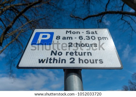 A street sign giving notice of parking restrictions.